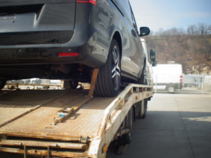 car hooked on the back of a flatbed tow truck