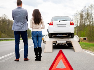 man and woman couple standing on the side of the road as their car gets put on a tow truck