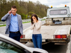 man on phone standing by a tow truck while his girlfriend stands by broken down car