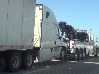 tow truck towing a white semi-truck after it broke down